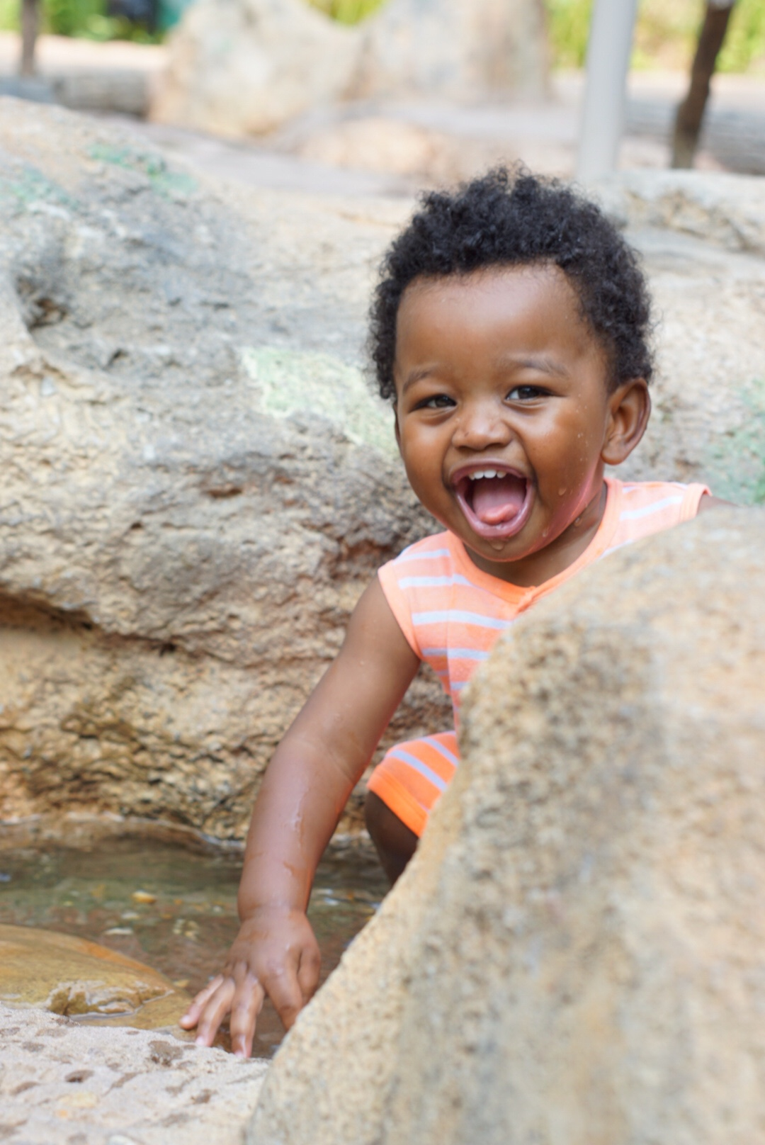 Toddler Boy Avery excited playing in water stream at Fernbank Museum in Atlanta, GA. Shot by Atlanta Lifestyle Photographer Crystal King of Just The Kings. We also shoot engagement photos, wedding photos, pregnancy photos, birthing photos, and family portraits in Austell, Powder Springs, Vinings, Marietta, Cobb County, and surrounding Metro Atlanta. Visit us at www.justthekings.com